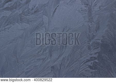 Frosty Beautiful Pattern On Winter Glass, Natural Texture. Blue Frosty Glass Ice Background. Winter
