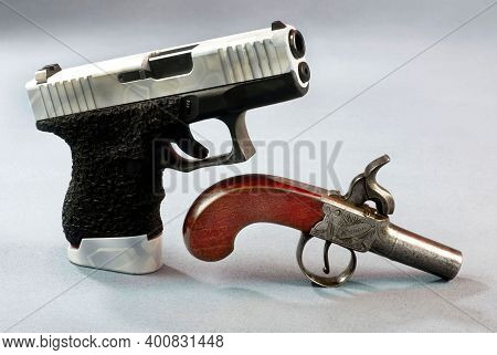 Old School And New School Pistols , One With 40 Caliber Semi Auto And Cap And Ball Antique.
