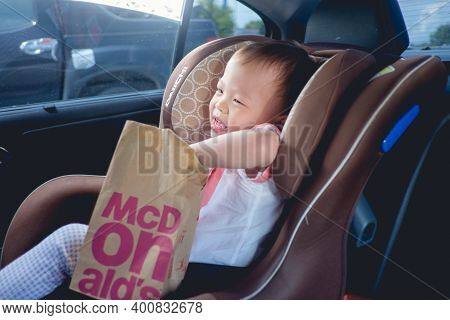 Bangkok, Thailand - June 5, 2018: Asian Toddler Boy Sitting In Car & Eating Fast Food After His Pare