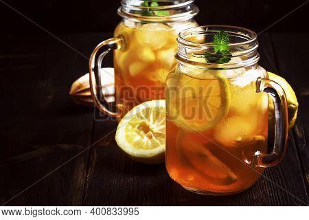 Black Ice Tea With Lemon Slice In Glass Jar On Dark Kitchen Table Background, Summer Cool Soft Drink
