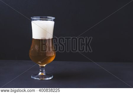 Beer Glass Tulip With Homemade Beer And Foam On Black Background.craft Beer Brewing From Grain Barle