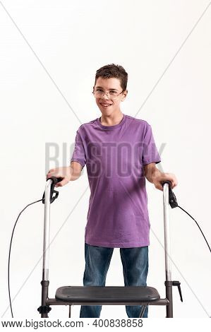 Teenaged Disabled Boy With Cerebral Palsy In The Glasses Smiling At Camera, Taking Steps With His Wa