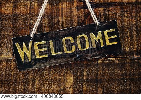 Wooden Welcome Sign Hanging On Space Wooden Background