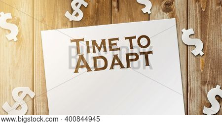 Text Time To Adapt Page, Paper Signs Of Dollar On Wood Table. Business Concept