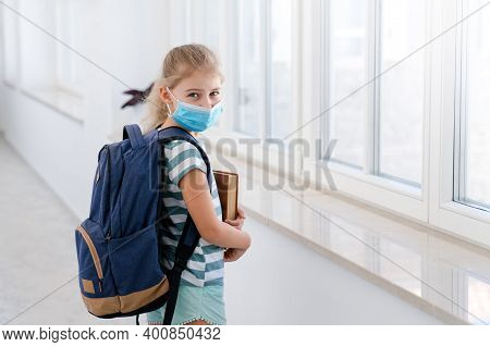 Kid In Protective Mask At School Inside. Kids Back To School. Child With Backpack And Book In Empty