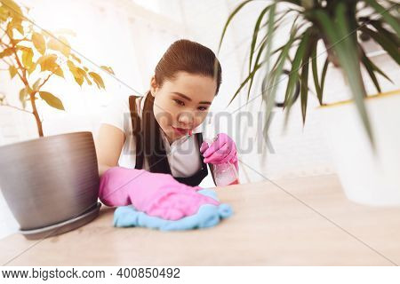 Adult Asian Maid Wipes Dust On Shelves In Room. Asian Cleaning Lady In Gloves Wipes Dust Off Shelves