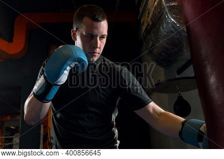 A Young Man Trains Punches On A Punching Bag In Blue Boxing Gloves In A Gym In The Background Of The