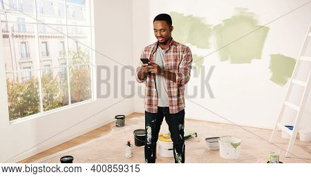 Handsome Cheerful Young African American Guy Texting On Smartphone Online Standing In Room During Ho