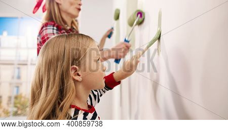 Side View. Close Up Of Caucasian Cute Little Kid Girl Helping Parents To Paint Wall In Green Color U