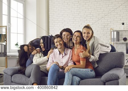 Group Of Happy Young Women Laughing And Fooling Around During Fun Get-together At Home
