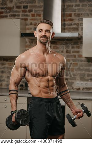 A Muscular Man With A Beard Is Posing With Dumbbells In His Apartment. Bodybuilder With Tattoos On H