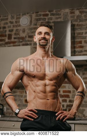 A Muscular Man With A Beard Is Posing In His Apartment. An Athletic Guy With Tattoos On His Forearms