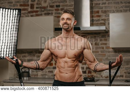 A Muscular Man Is Working Out With An Elastic Pull Rope In His Apartment. An Athletic Guy With Tatto
