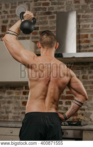 A Photo From The Back Of A Muscular Man Who Is Pushing A Black Weight In His Apartment. An Athlete W
