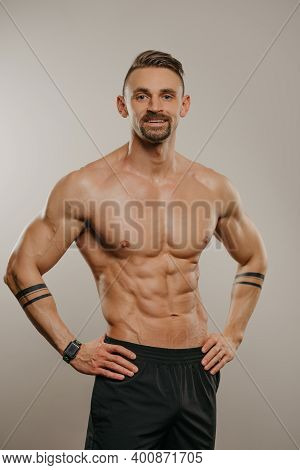 A Muscular Man With A Beard Is Posing. The Athletic Guy With Tattoos On His Forearms Is Demonstratin