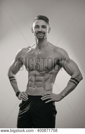 A Black And White Photo Of A Muscular Man With A Beard Who Is Posing. The Athletic Guy Is Demonstrat