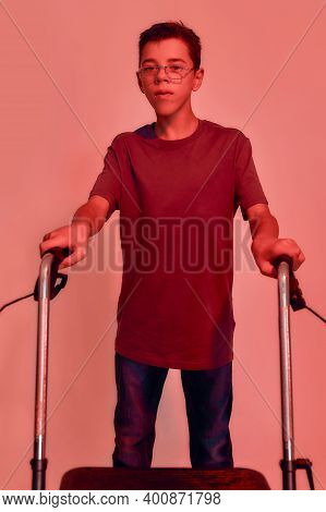 Portrait Of Teenaged Disabled Boy With Cerebral Palsy In Glasses Looking At Camera, Taking Steps Wit