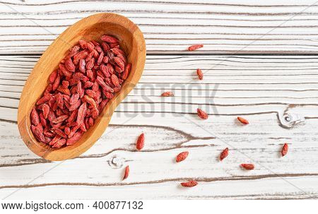 Dried Goji Aka. Wolfberry Seeds In Wooden Bowl And Spilled On White Boards Desk Near