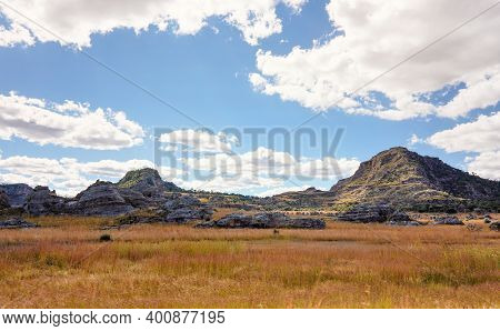 Low Grass Growing On African Savanna, Small Rocky Mountains In Background - Typical Scenery At Isalo