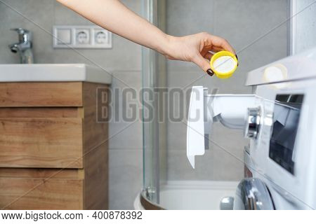 Female Hand Putting Washing Powder Into The Washing Machine Drawer. Washing Linen And Clothes Idea.