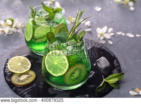 Non-alcoholic Mojito Cocktail In A Glass With Syrup, Fresh Mint, Lime And Kiwi Slices, Sparkling Wat