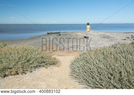 Little Boy In A Yellow Shirt Strollingin  In The Arid Land Of Camargue Region Of France During A Sun