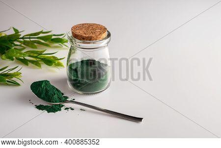 Spirulina Chlorella Algae Powder In A Glass Jar And In A Spoon On A White Background.