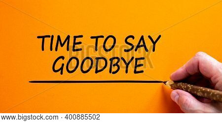 Time To Say Goodbye Symbol. Hand Writing 'time To Say Goodbye', Isolated On Beautiful Orange Backgro
