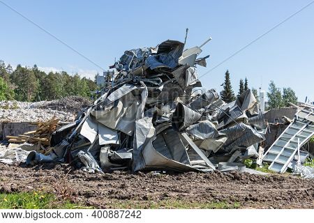 Pile Of Scrap Metal From A Dismantled Building At A Demolition Site. Industrial Background.