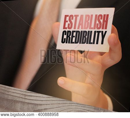 Businessman Holds Card With Text Establish Credibility In Hand. Business Concept