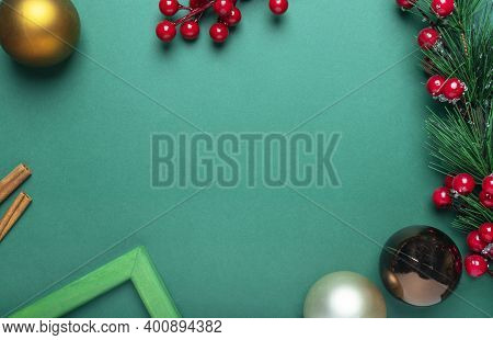 Christmas Banner Of Green Color With Place For Text And Frame Of Fir Tree Branch, Cinnamon, Baubles