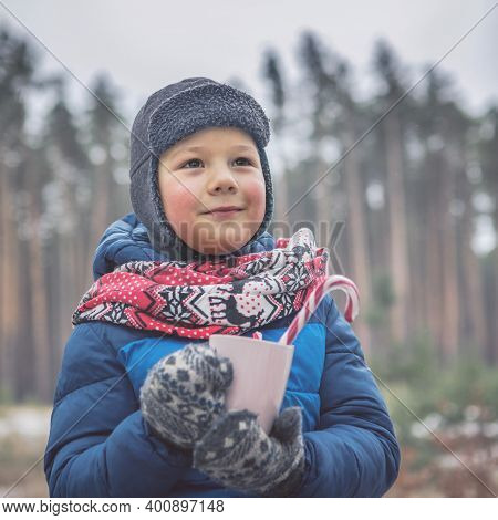 Kid In Winter Clothes Holds Christmas Cup. Kid During Stroll In A Snowy Winter Park. Beautiful Winte