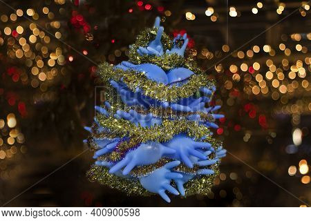 Christmas Tree Made Of Blue Medical Gloves Against The Background Of A Garland Of Protective Masks.