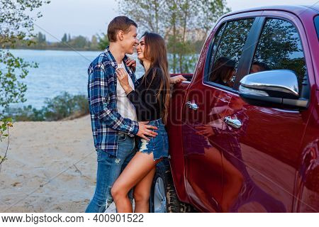Happy Young Couple In Love Smiling And Hugging Next To Red Car On The Beach Near The Lake. Young Cou