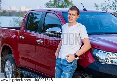 Young Guy In Jeans And A White T-shirt Near A Red Car On The Lake