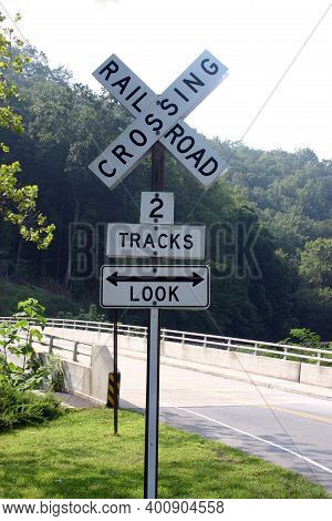 Old Railroad Crossing Sign By A Bridge Warning Of Two Tracks And Saying