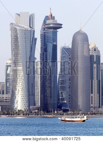 A dhow passes beneath some of the most massive buildings in Doha, Qatar, shortly before sunset in December 2012 poster