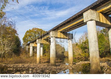 Augusta, Ga Usa - 12 12 20: Augusta Canal Trail A Train Bridge Over A River And Rock Bed