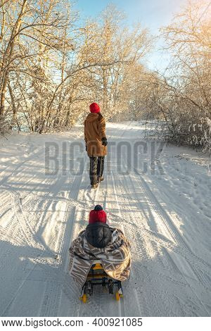 Mother With A Child Walks On A Frosty Winter Morning On A Sunny Day. Baby Wrapped In A Blanket Rides