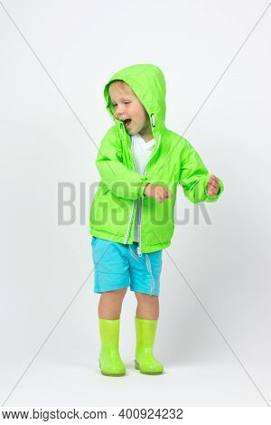 Child Boy In Bright Lime Green Jacket And Rubber Boots Laughs And Dances On White Background. Vertic
