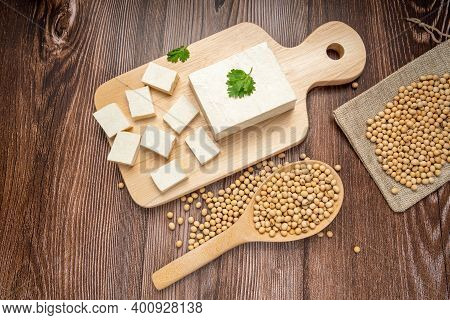 Whole Fresh Tofu And Diced Tofu On Wood Cutting Board With Soy Bean In Wooden Spoon. Full Depth Of F