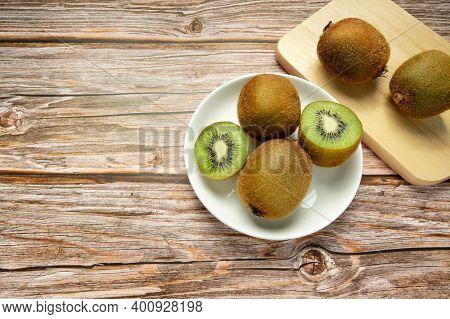 Ripe Whole Kiwi Fruit And Half Kiwi Fruit In White Dish And Kiwi On Wooden Cutting Board. Full Depth