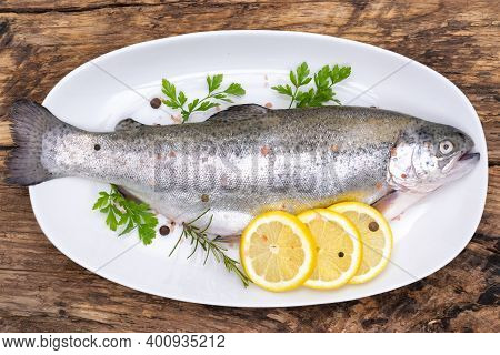 Top View Of A Raw Rainbow Trout Marinated In Fresh Herbs And Lemon Ready For Cooking On A Plate In R