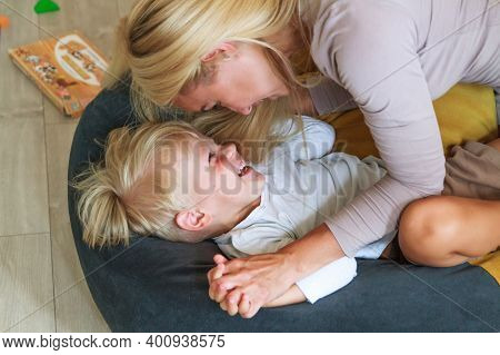 Mom Gently Hugs Her Little Son, They Have Fun