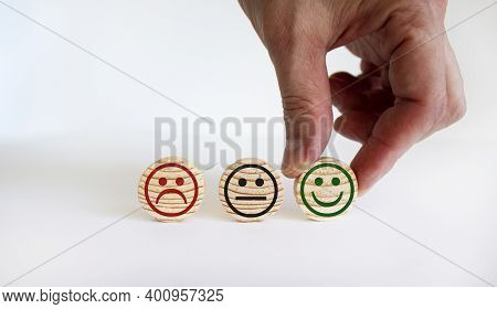 Various Emoticons Made Of Wooden Circles Drawn Lines Of A Mouth. Businessman Chooses Positive Smile.