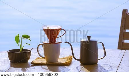 Drip Coffee Cup Set With Green Plant In Flower Pot On Wooden Round Table Against Riverside View Back