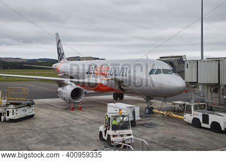 AUCKLAND AIRPORT, NEW ZEALAND - CIRCA 2016: Airliner of Jetstar Airways at Auckland Airport connected to jetbridge for boarding. Jetstar is an Australian low-cost airline