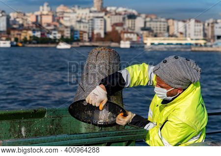 Istanbul, Turkey - 9 December 2020: Mussel Fisher At Work