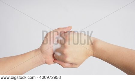 Male Model Is Interlock Fingers And Rub Mid-joints With Foaming Hand Soap On White Background.