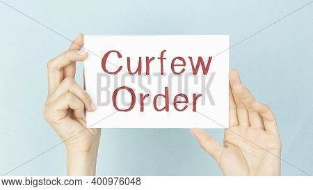 Curfew Order Text Words Inscription On White Paper In Male Hand On White Background